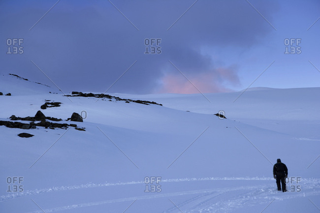 Man Walking Through The Mountain Snow