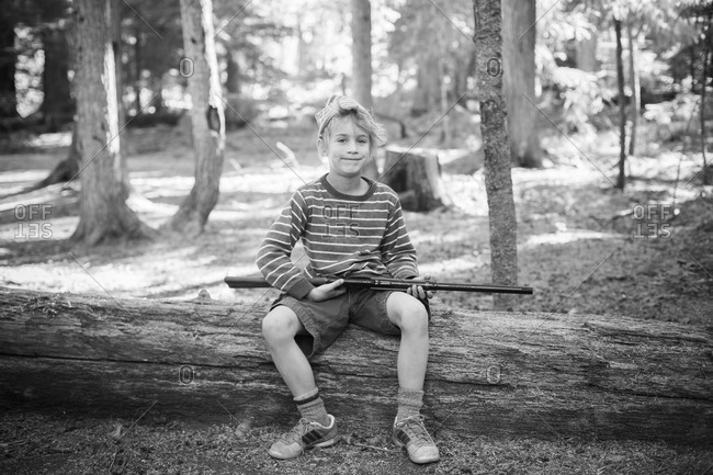 a young boy poses with a bb gun