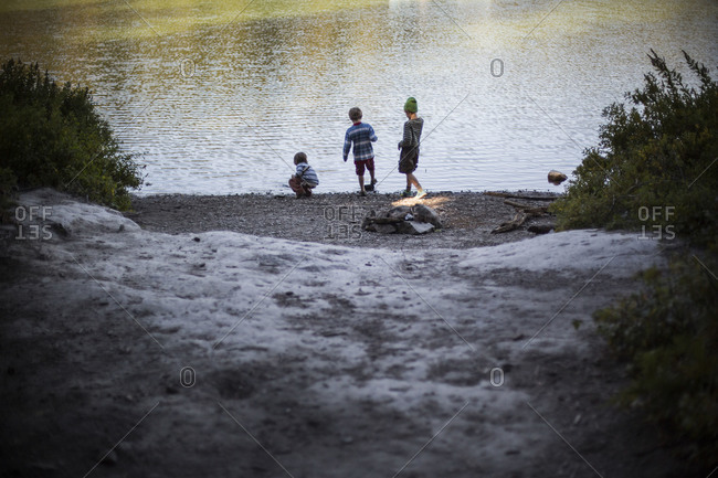 three young boys play together by a lake