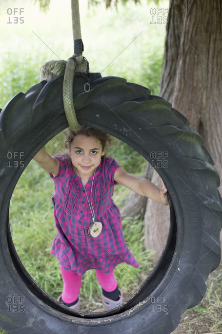 a young girl plays with a tire swing