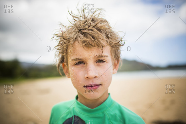 a young boy poses while on a beach
