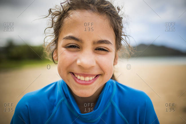 a young girl smiles while on a beach