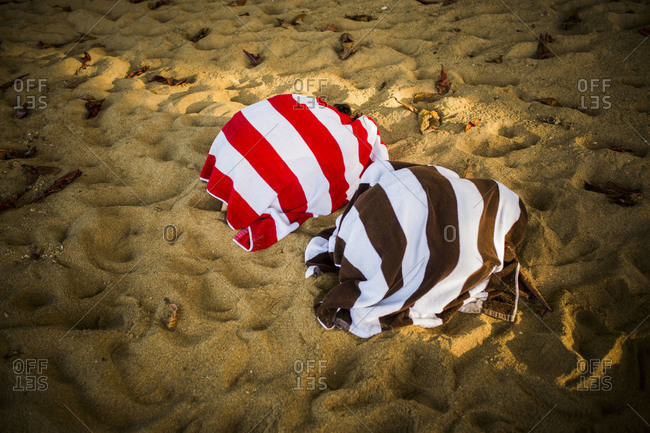 two kids hide under striped towels on a beach