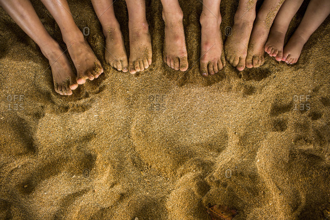 Five pairs of feet in the sand of a beach