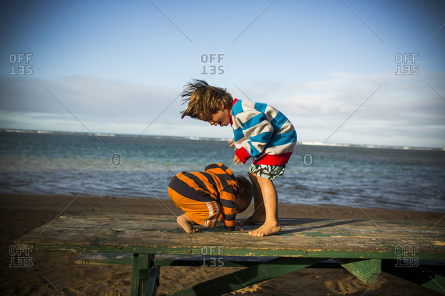 a toddler attempts to stand on a picnic table