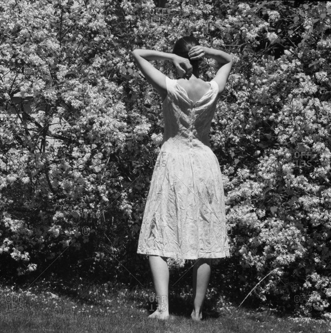 Back-view of a young woman standing in the garden