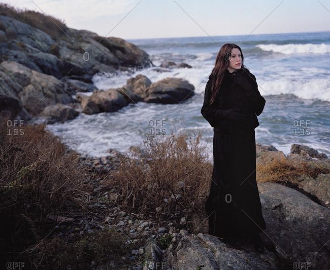 Woman in vintage mourning outfit, standing in front of rocky surf