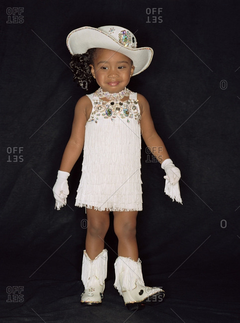 Child Beauty Queen Wearing Jewel Studded Hat And Fringed Gloves With Boots And Dress