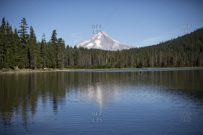 Tranquil scene of pond mountain peak in the background.
