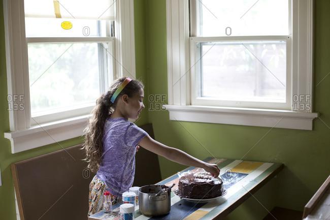 Little girl preparing birthday cake in the kitchen