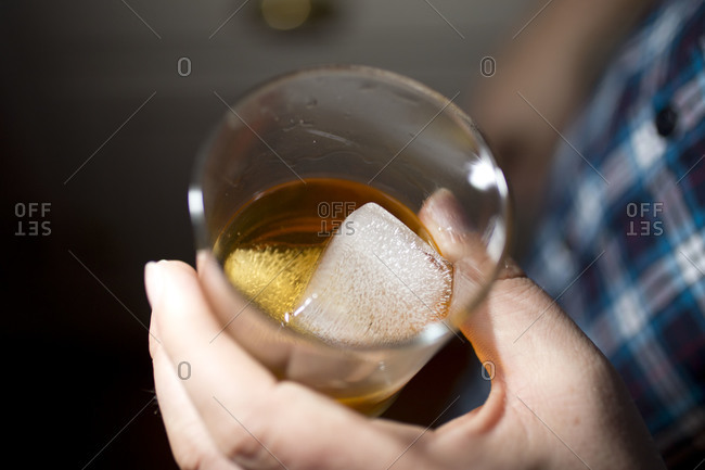 Glass of alcoholic beverage with ice cube, closeup