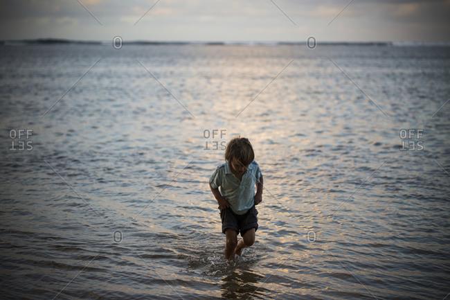 Caucasian boy walking in the water.