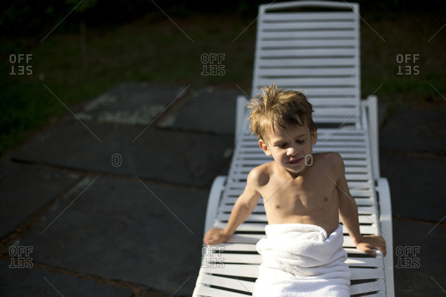 Little boy wrapped in white towel sitting on plastic deck chair.