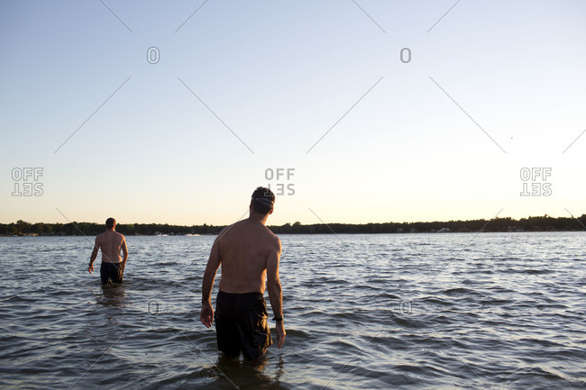 Two men walking in the water.