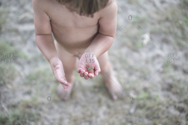 Undressed little boy holding little frog in his hand.