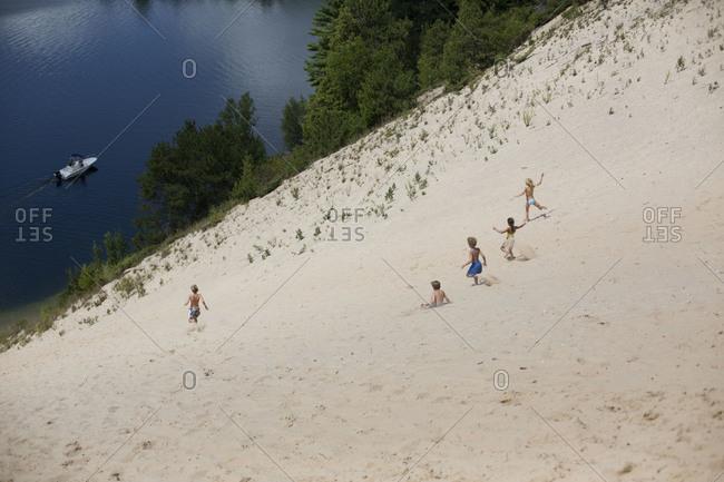 Kids running down sand slope.