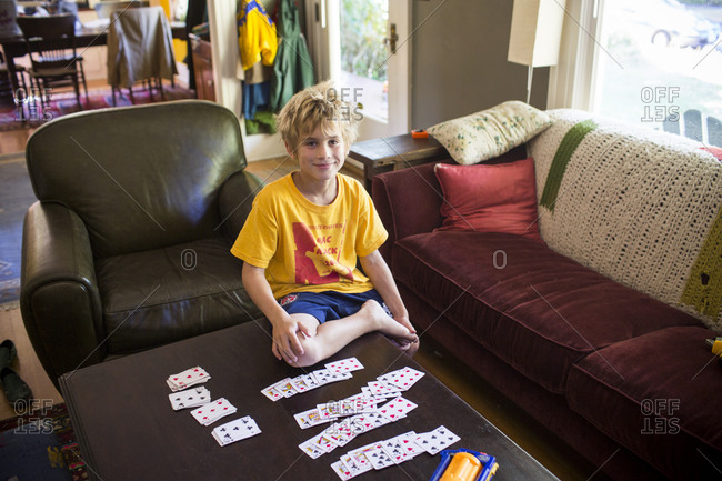 A boy playing Klondike card game at the coffee table.