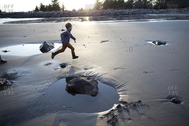 A little child running among puddles at beach.