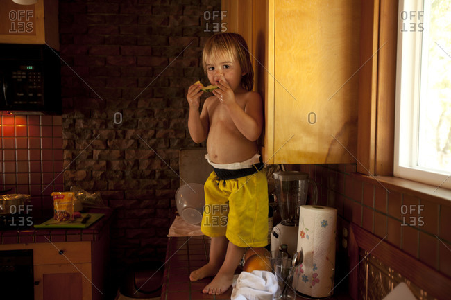 A toddler boy standing on kitchen's counter and eating slice of honeydew.