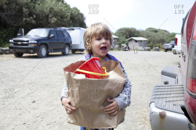 A little boy carrying brown bag with full of toy.