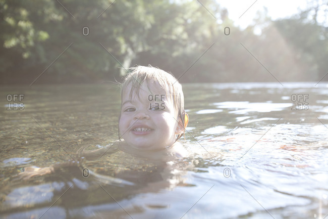 Caucasian toddler swimming in the shallow water.