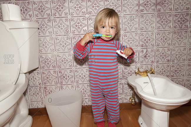 A little toddler washing his teeth in bidet.