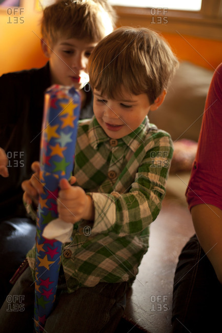 A boy unwrapping a gift.