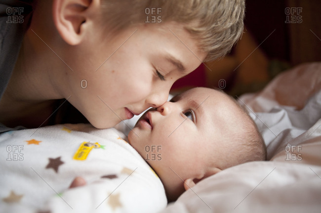 Close-up of little boy with newborn baby.
