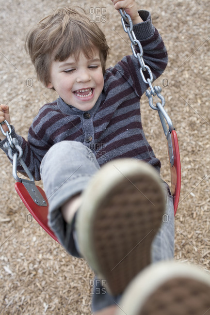 Cute young boy swings at kid park playground.