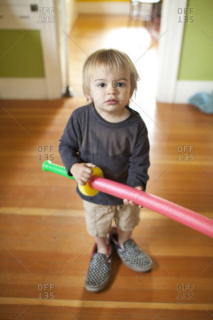 A toddler wearing huge sneakers and holding toy foam sword.