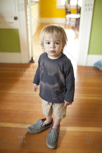 A toddler wearing huge sneakers.