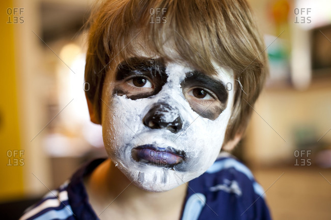 Portrait of boy with painted face and sad eyes.