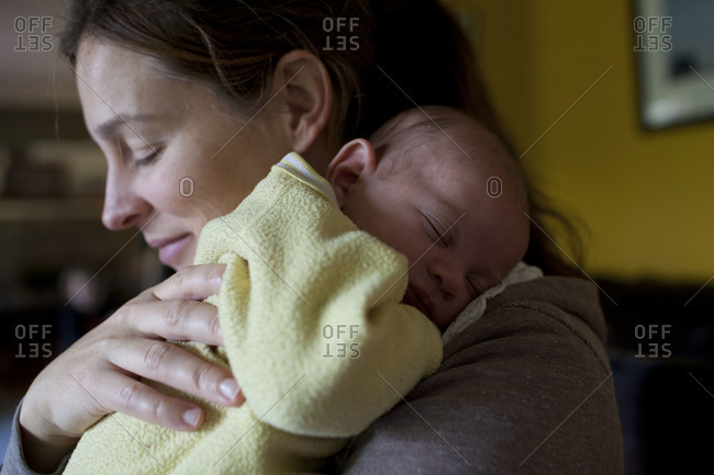 Newborn baby on mother's shoulder.