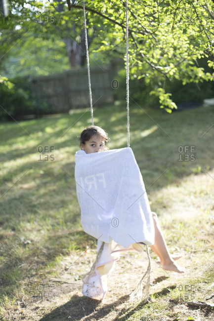Young girl sitting on swing in garden