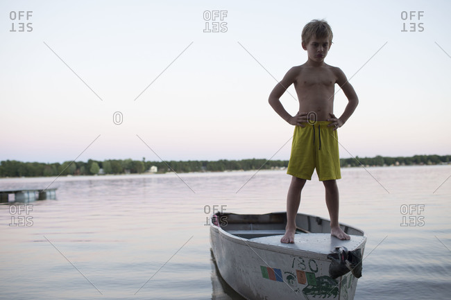 Displeased boy standing on boat
