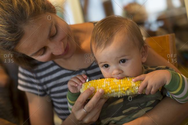 Young Caucasian woman feeding her son corn