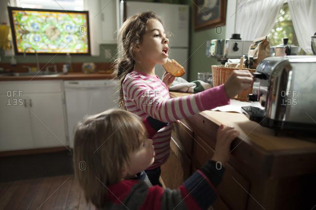 Children preparing toast in kitchen