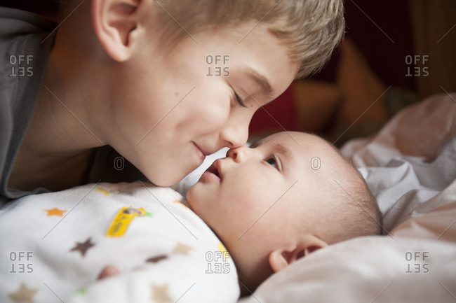 Boy kissing his young brother