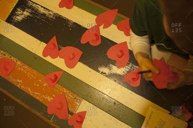 Top view of boy preparing red paper hearts
