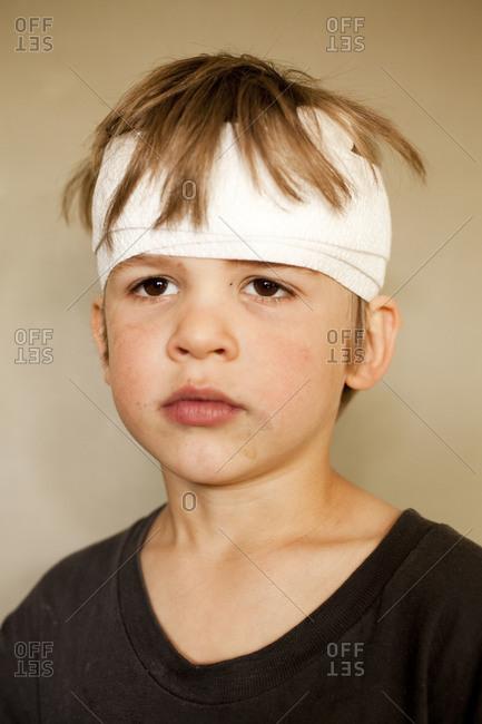 Portrait of boy with head bandage