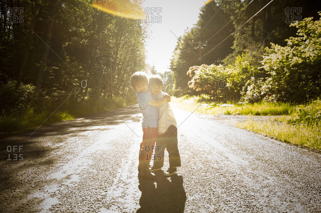 Little brothers embracing in the middle of the road