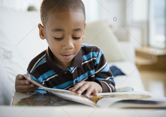 African American boy reading book on sofa