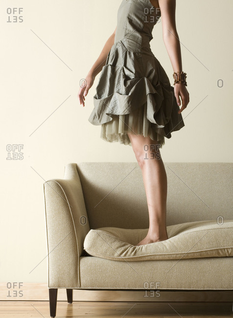 A woman in a dress stands on a couch