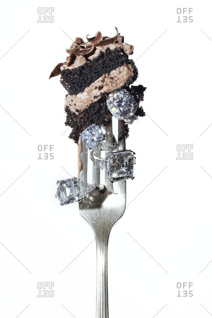 A piece of cake and diamond rings on a fork