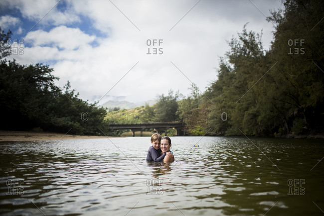 Caucasian mother and her son together in small pond