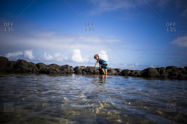 Young Caucasian boy playing in tidal pool