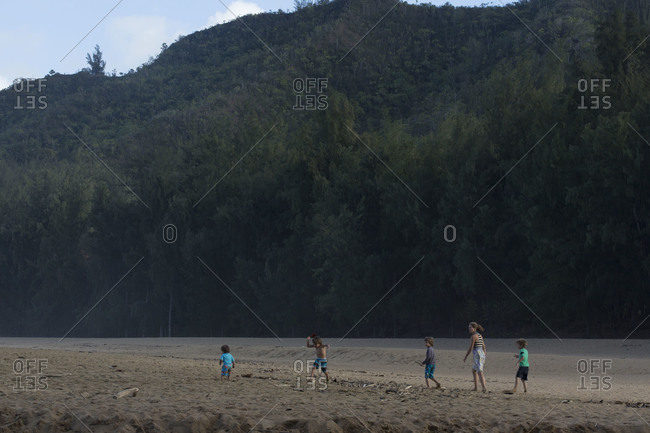 Young Caucasian mother and children together on open beach at edge of forest