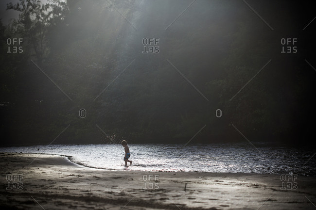 Young Caucasian child plays on sandy edge of pond