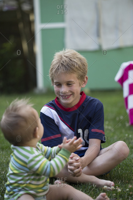 Little boy playing with his baby brother in the yard