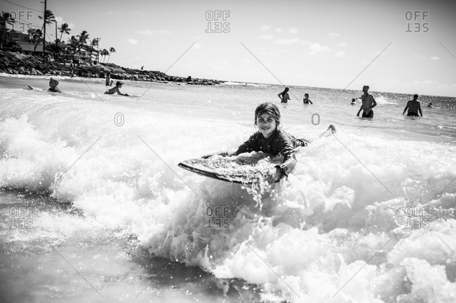 Black and white image of young Caucasian boy on boogie board